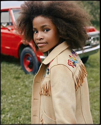 Girl wears tan beaded fringe deerskin jacket.