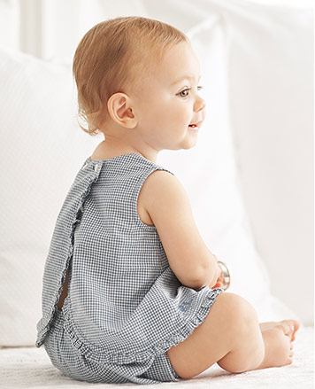 Baby girl wears checked ruffled top with an open back and matching shorts.