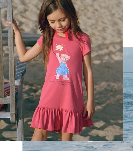 Girl wears ruffled-hem tee dress with Polo Bear at front.