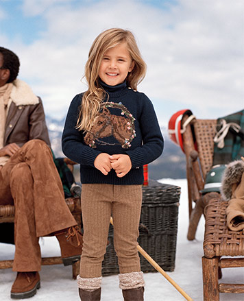 Girl wears navy sweater with horse graphic at center.