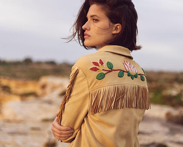woman wears fringed suede jacket