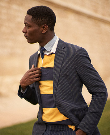 Man in pinstripe suit paired with yellow & navy rugby shirt