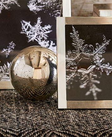 Snowflake photographs in silver frames next to silver ornament