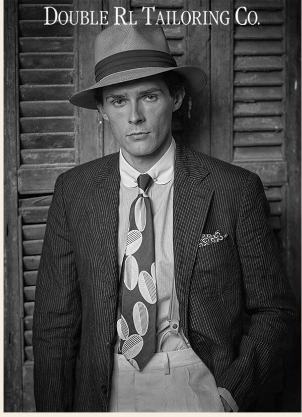 Man in suspenders, pinstripe jacket & brimmed hat