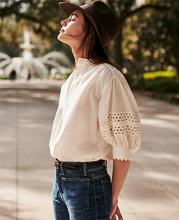 Woman in white top with eyeylet blouson sleeves