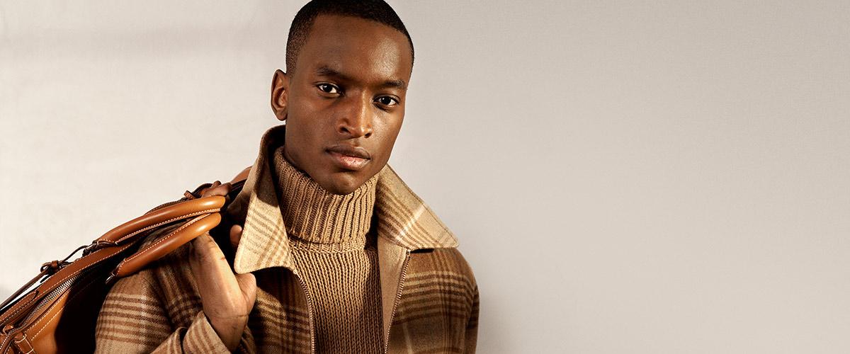 Man in tan turtleneck sweater and Glen plaid jacket carrying bag over shoulder