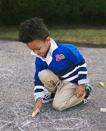 Boy in long-sleeve Polo shirt draws on street with chalk.