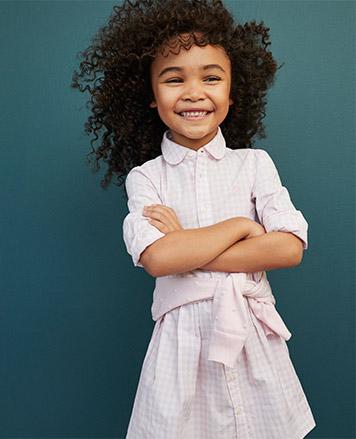 Girl wears light pink gingham shirtdress.