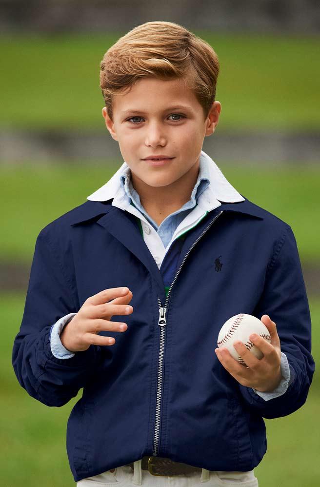 Boy wearing chino jacket holds baseball.