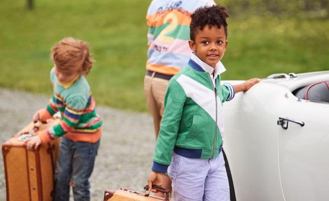 Boy holding suitcase wears green zip-up jacket.