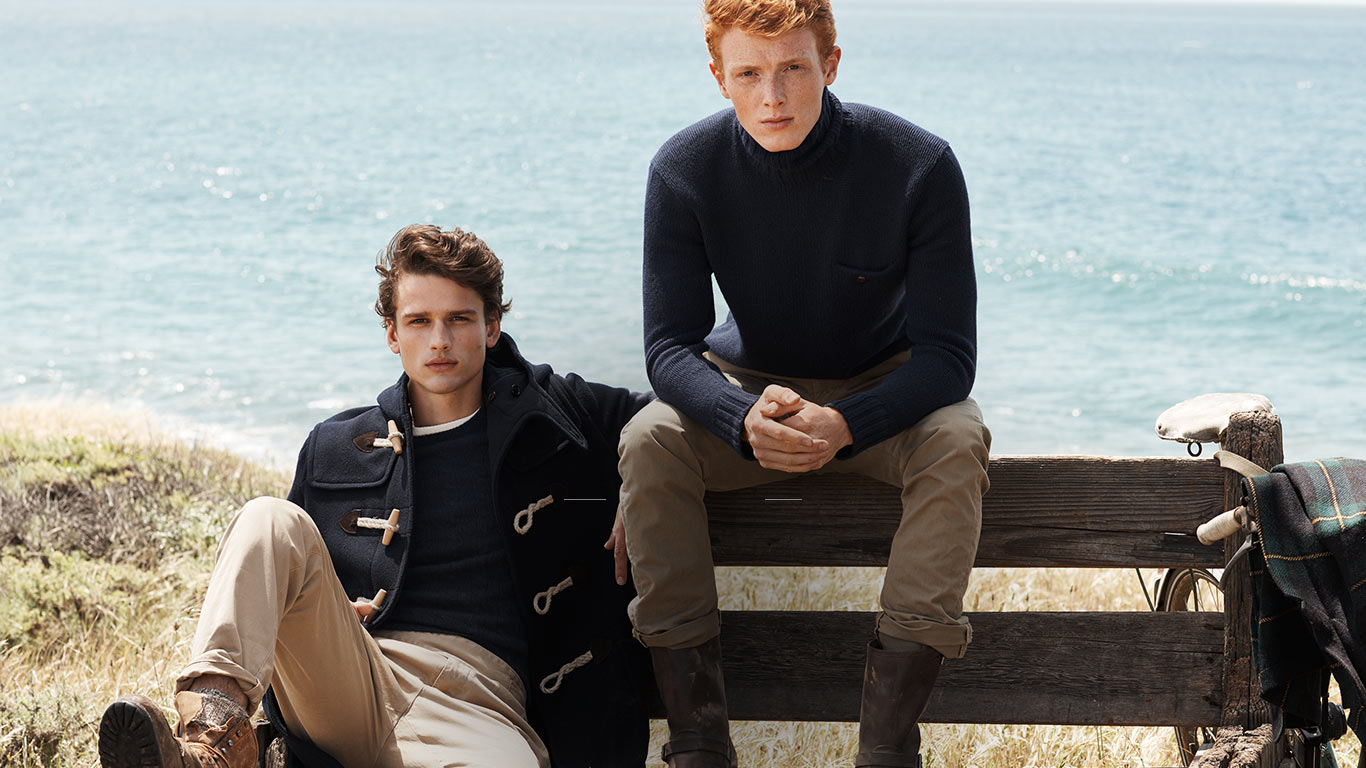 Man in toggle coat & man in turtleneck by water