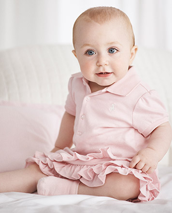 Baby girl wears light pink Polo dress with ruffles.