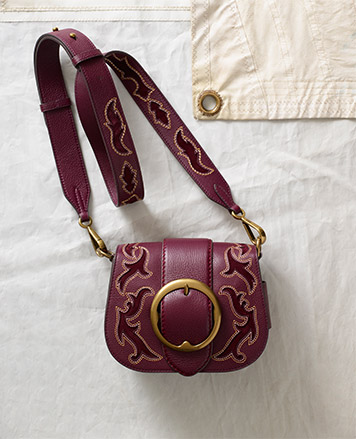 Berry-hued leather shoulder with suede trim and large buckle