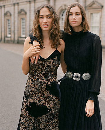 Woman in spaghetti-strap floral dress & woman in pleated dress