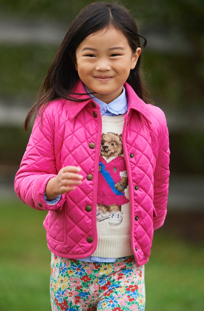 Girl wears pink quilted jacket over Polo Bear sweater.