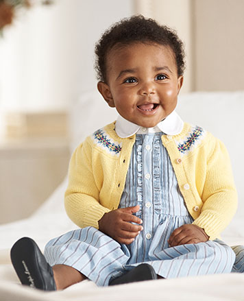Baby girl wears striped blue shirtdress with yellow cardigan.