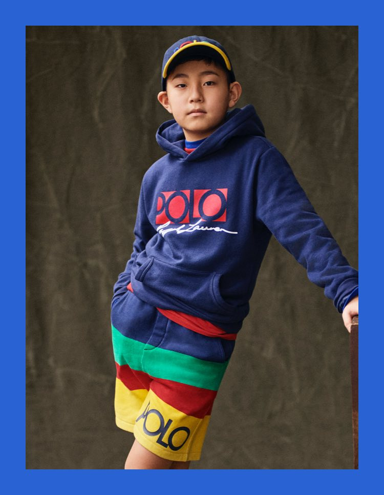 Boy in navy Polo hoodie & multicolored striped shorts