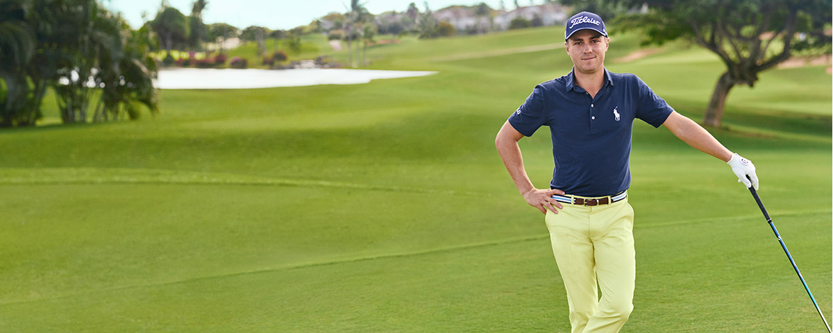 Justin Thomas on green in navy Polo shirt with embroidered Polo Pony