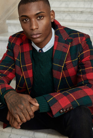 Man in tartan blazer layered over pine green cable sweater