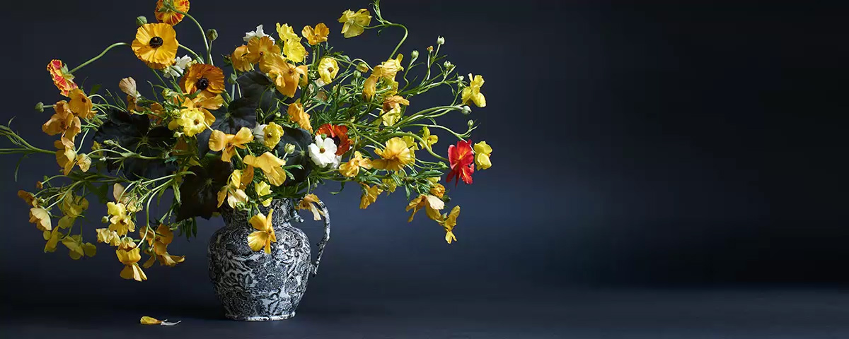 Navy pitcher used as vase for yellow wildflower arrangement
