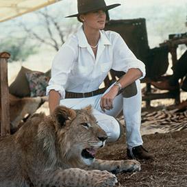 Woman in safari-inspired apparel petting lion