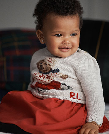 Baby girl wears ice-skating bear sweater and red skirt.