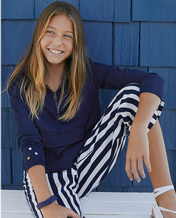 Girl wears navy sweatshirt and blue-and-white striped pants.