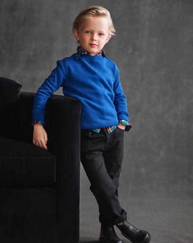 Boy wears blue sweater over plaid button-down and black pants