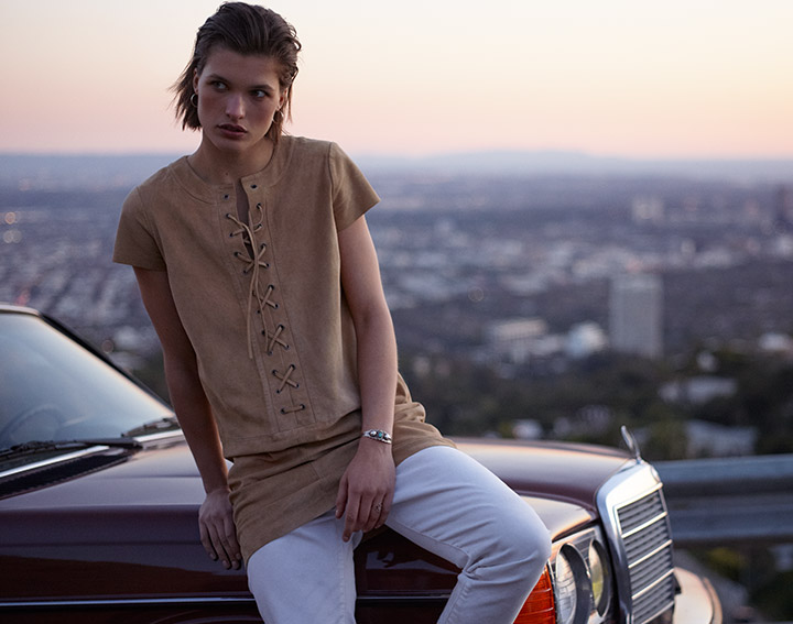 Woman in tan suede lace-up dress leans against car