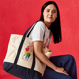 Patti Harrison carrying large canvas rainbow Pony tote bag
