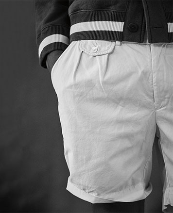 Close-up of white shorts with subtle pleats & front flapped pockets