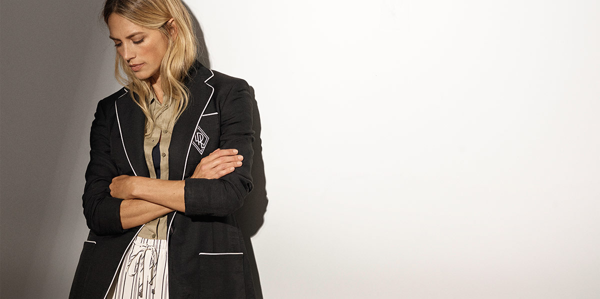Model wears striped pants and black blazer with white piping and LRL crest at chest.
