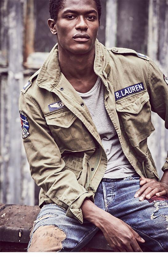 Man in army green field jacket, grey tee & distressed denim