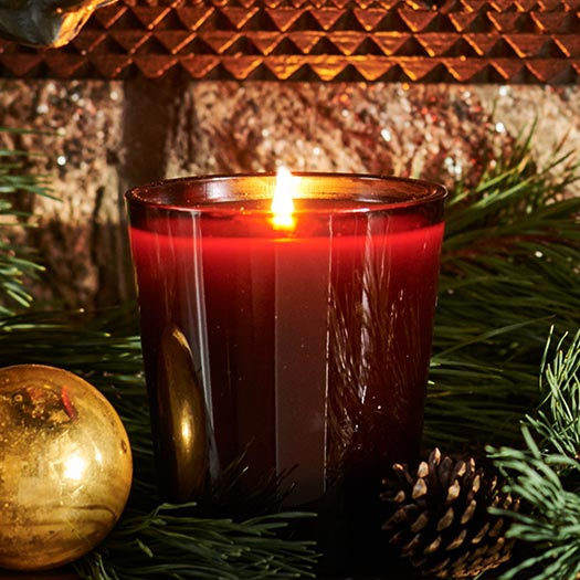 Lit holiday candle surrounded by pine needles.