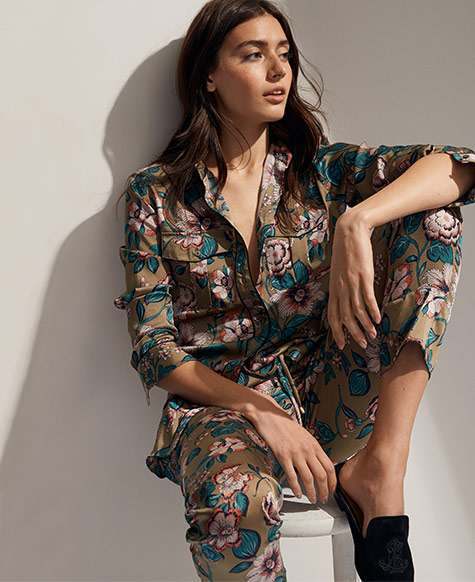 Woman in bold floral-print blouse with matching pants