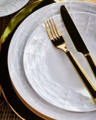 Golden-hued flatware on white porcelain plates with tonal pattern