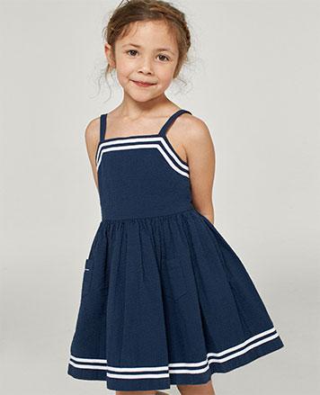 Girl wears navy-and-white seersucker dress.