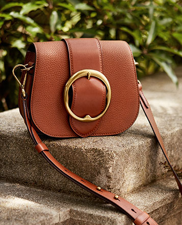 Brown leather shoulder bag with large buckle at front