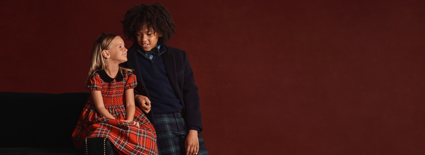 Girl wears red plaid dress; boy wears plaid pants and navy half-zip.