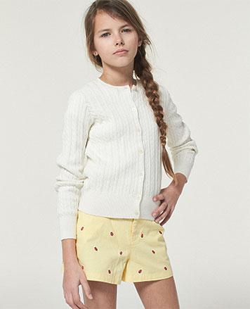 Girl wears ladybug-embroidered shorts with white cardigan.