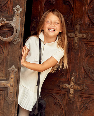 Girl wears white Polo dress with pleated skirt.