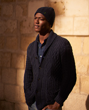 Man in navy shawl-collar cardigan & knit hat