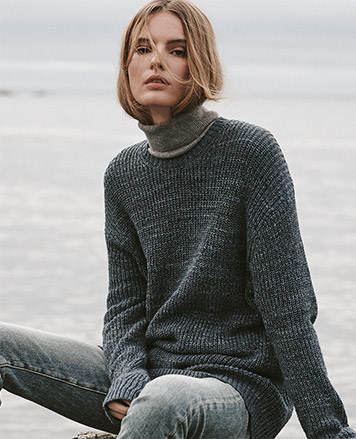 Woman in sweater & turtleneck by water