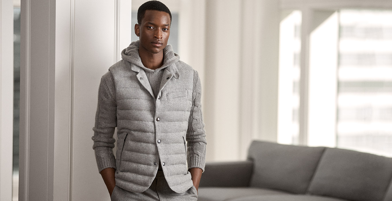 Model in grey quilted vest over grey hooded sweater