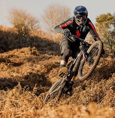 Photograph of Sam Reynolds mountain biking on uneven terrain