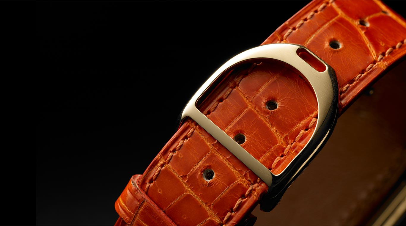 Close-up of alligator strap and stirrup-shaped buckle.