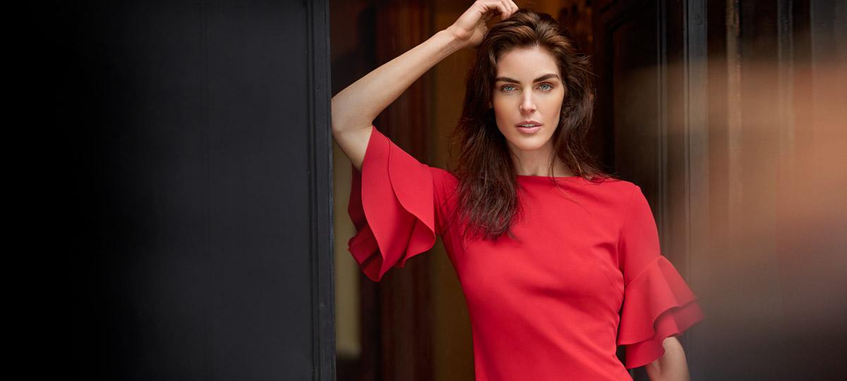 Image of model Hilary Rhoda in red bell-sleeve dress