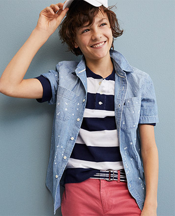 Boy wears paint-splattered chambray button-down and red chinos.