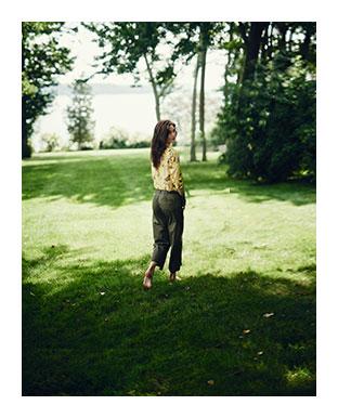 Model walks on lawn in olive-hued pants & floral top