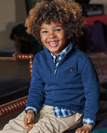Boy wears blue half-zip sweater over plaid button-down shirt and chinos.